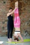 要做在舒展的瑜伽锻炼的辅导员帮助 免版税库存照片