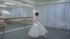 要做在镜子前面的fouette的年轻芭蕾舞女演员火车有在明亮的芭蕾类的纬向条花的 影视素材