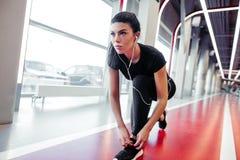 要做鞋带的下来女孩在健身健身房在连续锻炼锻炼前 免版税图库摄影