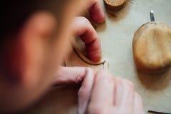 主要工匠luthier工作在小提琴的创作 在木头的刻苦细节工作 库存图片