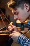 主要工匠luthier工作在小提琴的创作 在木头的刻苦细节工作 免版税图库摄影