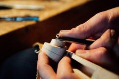 主要工匠luthier工作在小提琴的创作 在木头的刻苦细节工作 免版税库存图片