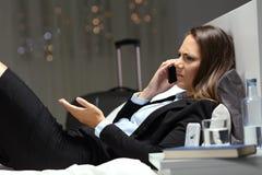 要求在电话的恼怒的女实业家在旅馆客房 免版税图库摄影