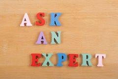 要求在从五颜六色的abc字母表块木信件组成的木背景的一个专家的词,复制广告文本的空间 库存照片