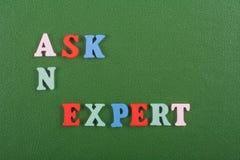 要求在从五颜六色的abc字母表块木信件组成的绿色背景的一个专家的词,复制广告文本的空间 免版税库存照片