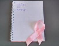 要知道的事在与桃红色丝带了悟乳腺癌的笔记薄被写 库存图片