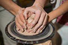 主要陶瓷工教孩子如何从黏土做水罐 库存照片