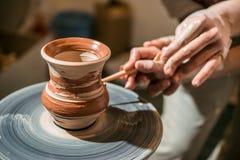主要陶瓷工教孩子如何从黏土做水罐 免版税库存图片