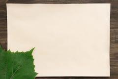 覆盖与一片葡萄叶子的老葡萄酒纸在年迈的木背景 食物健康素食主义者 免版税库存照片