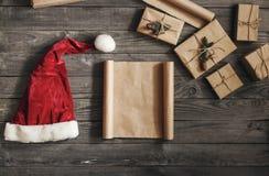 覆盖与圣诞节礼物和圣诞老人帽子,顶视图的纸 图库摄影