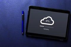 覆盖在片剂屏幕上的上载的概念有在蓝色样式的蓝色笔的 免版税库存图片