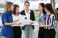 见面在与文书工作的一个会议和文件的小组年轻女实业家在办公室外在都市城市 免版税库存照片