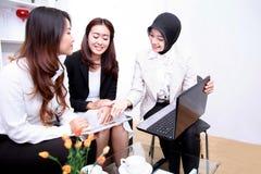 见面在办公室客厅的一个小组年轻女实业家 库存图片