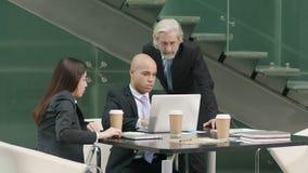 见面在办公室的三企业经营者谈论事务使用便携式计算机 股票录像