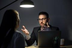 见面在办公室的两买卖人在晚上 免版税库存图片