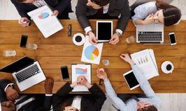 见面在办公室的小组繁忙的商人,顶视图 免版税库存照片
