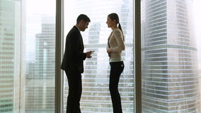 见面在办公室窗口附近的商人和女实业家,妇女晚 股票录像