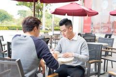 见面在咖啡店的两个亚裔商人画象  库存图片