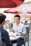 见面在咖啡店的两个亚裔商人画象  免版税库存照片