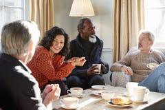 见面在咖啡店的表附近的小组中世纪朋友 免版税库存照片