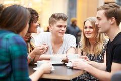 见面在咖啡馆的小组年轻朋友 库存图片