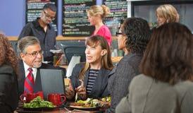 见面在咖啡馆的激动的工作者 免版税库存照片