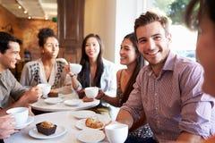 见面在咖啡馆餐馆的小组朋友 库存图片