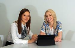 见面在有片剂个人计算机的办公室的两名女实业家 库存照片