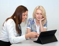 见面在有片剂个人计算机的办公室的两名女实业家 免版税库存图片