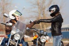 见面在有问候姿态的街道的两个欧洲女孩骑自行车的人 免版税库存照片