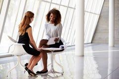 见面在现代办公室的招待会的两名女实业家 免版税库存照片