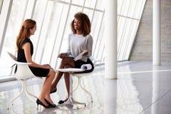 见面在现代办公室的招待会的两名女实业家 免版税库存图片