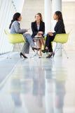 见面在表附近的三名女实业家在现代办公室 库存图片