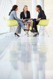 见面在表附近的三名女实业家在现代办公室 免版税库存照片