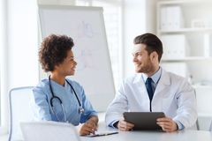 见面在医院办公室的两位愉快的医生 免版税库存图片