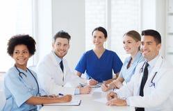 见面在医院办公室的小组愉快的医生 免版税库存图片