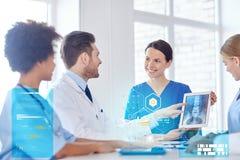 见面在医院办公室的小组愉快的医生 免版税库存照片