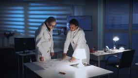 见面实验室的外套的两聪明女人改进控制电子学计划