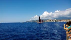 观众手表与猩红色的帆船在海航行 免版税库存图片