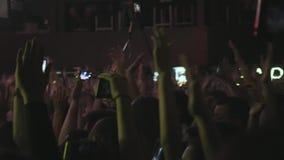 观众用手上升了在放出下来从阶段上的音乐节和光 很多人民与 股票录像