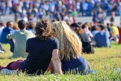 从观众的一对夫妇观看一个音乐会一起坐在草在海涅肯Primavera声音2014年 免版税图库摄影