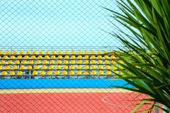 观众的论坛在有黄色位子的一个体育场内通过与一棵棕榈树的一个栅格在前景 库存照片