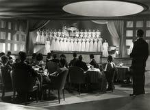 观众观看女性唱诗班在夜总会执行 免版税库存图片