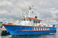 观光和宪章的蓝色小船 免版税库存照片