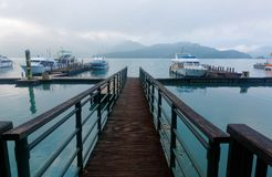 观光的小船早晨风景被停泊对一座木码头&有雾的山的浮船坞由湖边 免版税库存照片