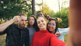 观点射击了少妇有照相机的保存设备和与朋友不同种族的小组的采取selfie在公园 股票录像