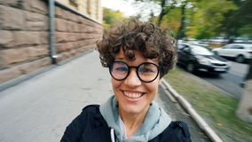 观点射击了戴看照相机和笑转过来的短发和眼镜的无忧无虑的小姐  股票视频