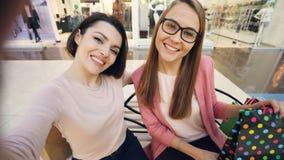 观点有被射击俏丽的女朋友采取与纸袋的selfie在购物中心和乐趣陈列舌头 股票录像