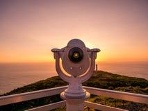 观点的图象与双筒望远镜的在指向海洋的五颜六色的日落期间 库存照片