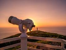 观点的图象与双筒望远镜的在指向海洋的五颜六色的日落期间 免版税库存图片